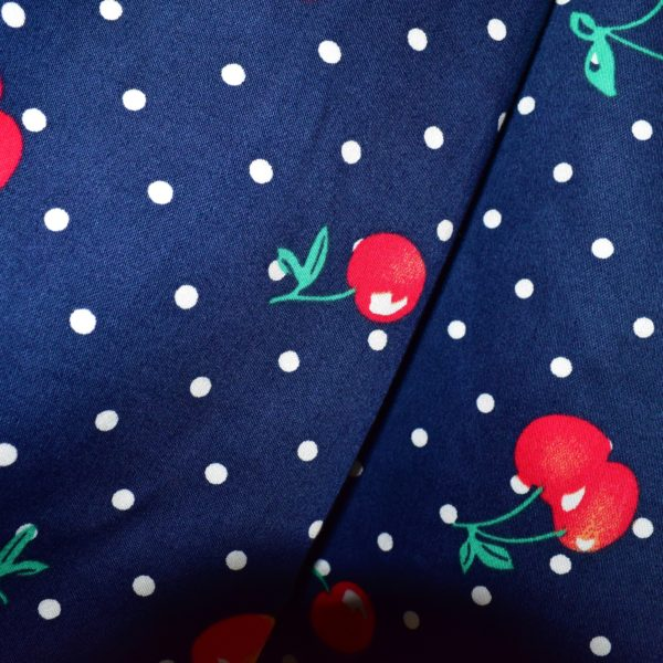 Close up of blue fabric with cherry and small white polka dot print