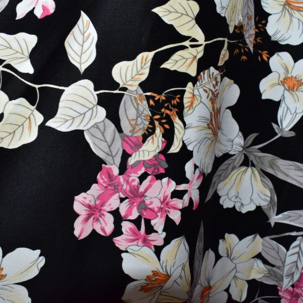 Close up of pink and white floral on black background fabric