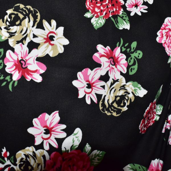Close up of black fabric with pink and green floral print