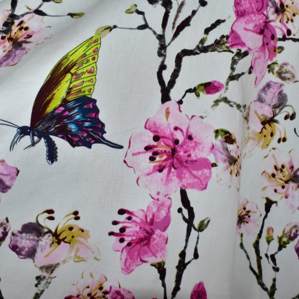 Close up of fabric with butterflies and blossom print on a white background