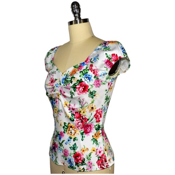Siren Clothing 50's vintage-inspired top with elasticated short sleeves and front pleat detail in white floral cotton spandex fabric, side view