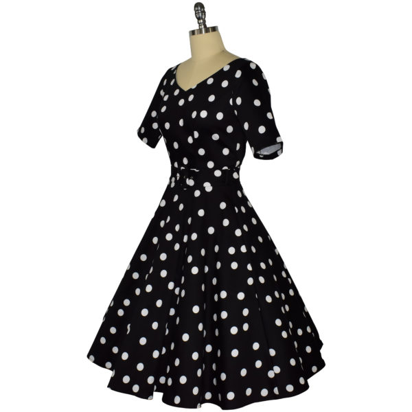Siren Clothing 50's vintage-inspired swing dress with sleeves in black and white polka dot fabric, side view